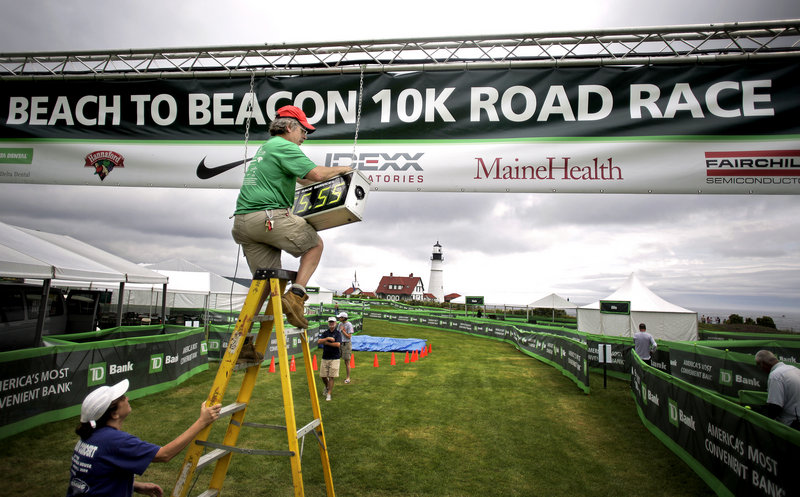 Steven Bedsole of Granite State Race Services installs the timing clock at the finish line of the TD Beach to Beacon 10K on Friday at Fort Williams Park in Cape Elizabeth. Holding the ladder is Anita Teschek.