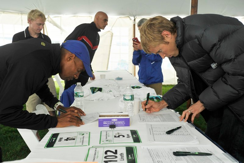 Ryan Hall, right, who didn't arrive in Portland until 2 a.m. Friday, and Meb Keflezighi – perhaps the top two American males in the Beach to Beacon – register and collect their bib numbers in advance of Saturday's race.