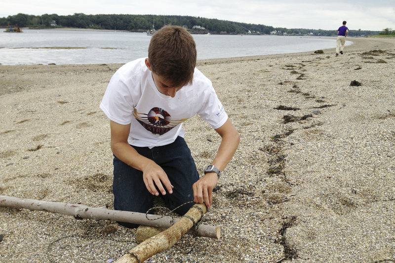 """Galen DuBois of Woolwich ties together tree limbs as he begins to build a raft that will be used to help """"rescue"""" him and 20 other students from Little Chebeague Island."""