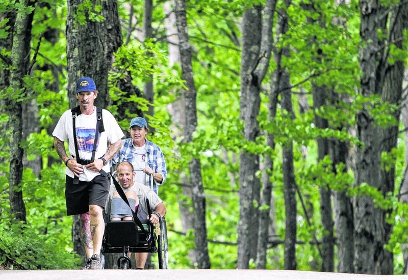 Jeff Cleveland, a paraplegic from Lyndonville, Vt., finishes a test drive of his modified wheelchair with the help of Dave Smith, front, and Sandy Olney in Sugar Hill, N.H. He will be making his first ascent of Mount Washington on Sunday.