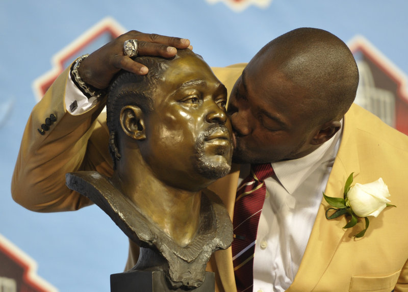 Former defensive lineman Warren Sapp shows his softer side as he kisses his own bust while being inducted in the Pro Football Hall of Fame in Canton, Ohio, on Saturday. Also inducted were Jonathan Ogden, Dave Robinson, Larry Allen, Bill Parcells, Curley Culp and Cris Carter.