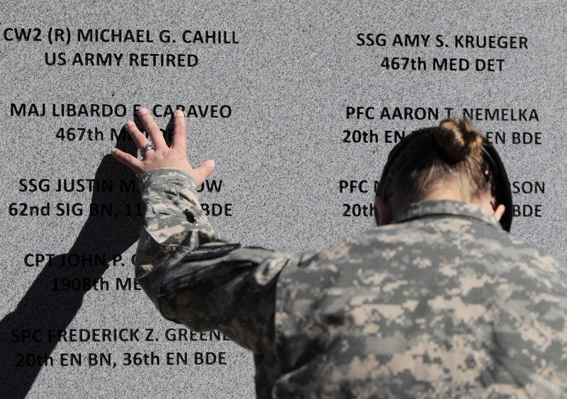Staff Sgt. Joy Clark runs her fingers over the engraved names of soldiers, victims of the worst mass shooting in history on a U.S. military base, during a November 2010 ceremony marking the one-year anniversary of the Fort Hood rampage.