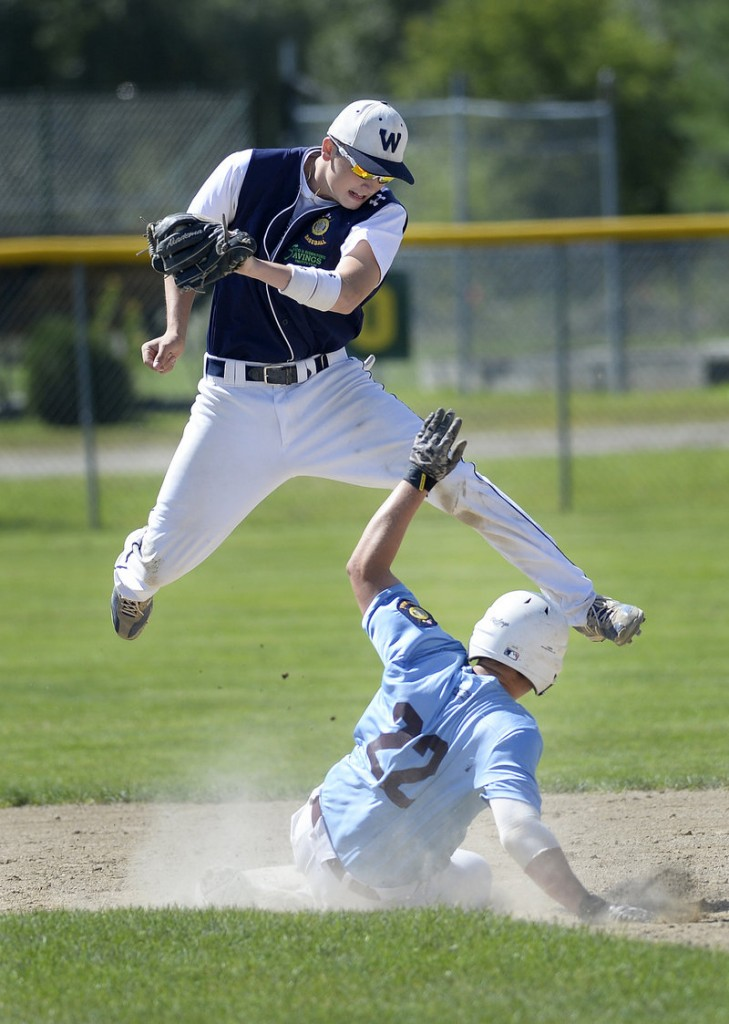 Windham's Jack Herzig slides under the tag of Westbrook infielder Brett Goodnow during Monday's American Legion championship game in Augusta. Windham won and advances into the Northeast Regional in Middletown, Conn.