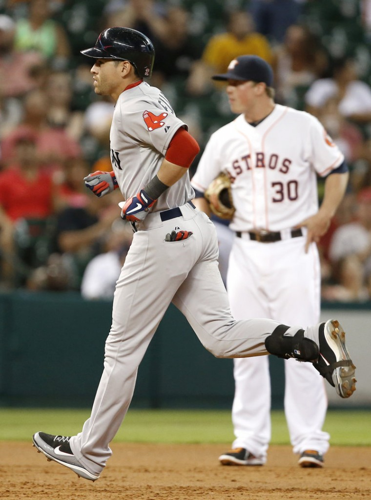 Jacoby Ellsbury of the Boston Red Sox rounds the bases in front of Houston Astros third baseman Matt Dominguez after homering.