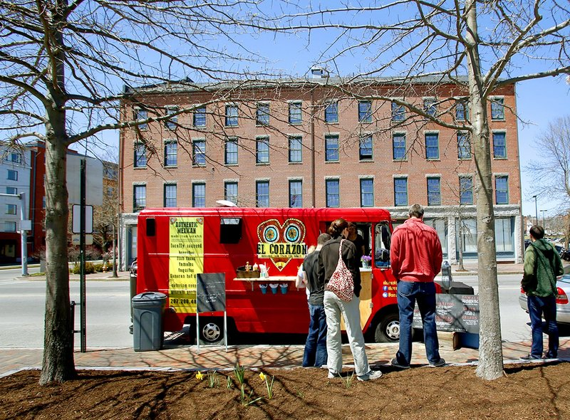 Diners line up at the El Corazon food truck parked on Commercial Street in Portland in a May file photo. The city's food truck ordinance makes it more difficult for food truck owners to operate in Portland, mobile vendors say.