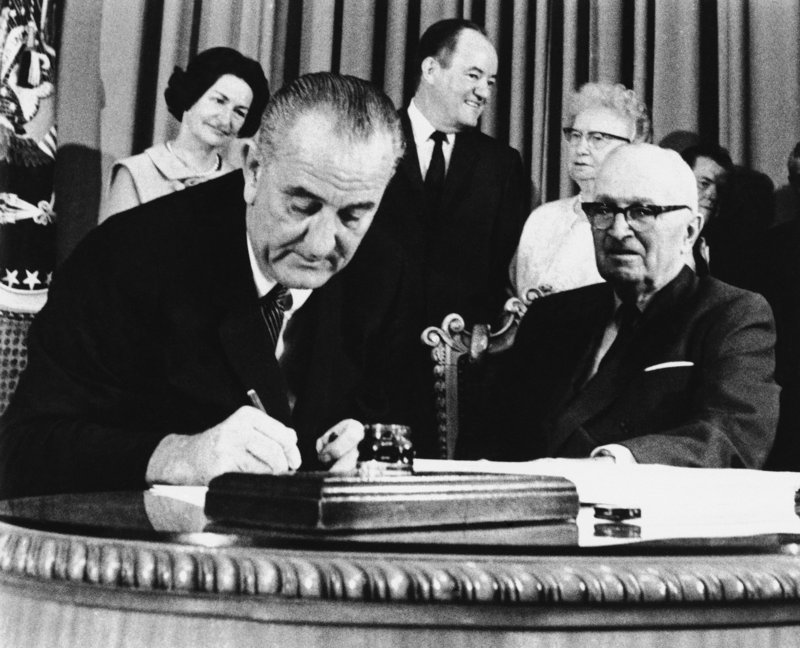 President Lyndon Johnson signs the Medicare bill into law July 30, 1965, as former President Harry Truman, right, observes at the Truman Library in Independence, Mo. A letter writer says the program is more cost-effective than private health insurance.