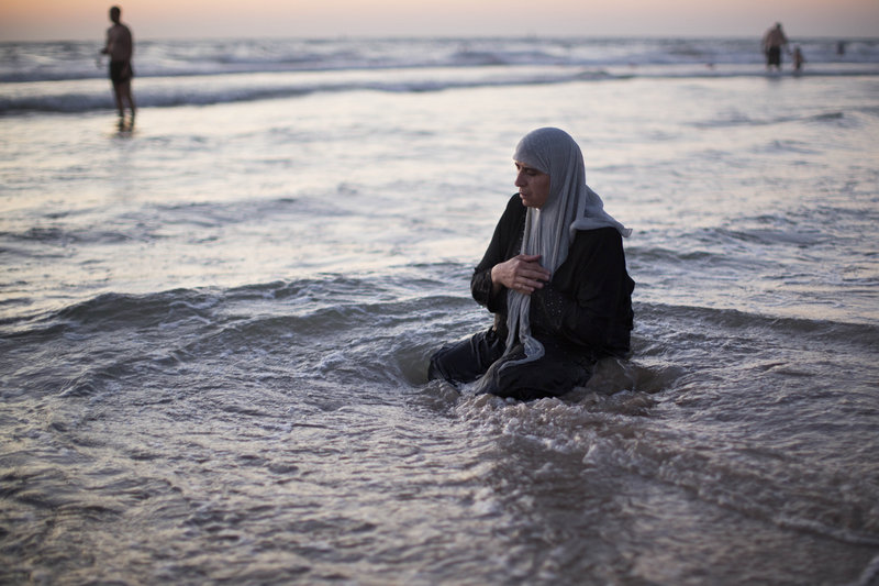 A Palestinian woman prays in the Mediterranean Sea in Tel Aviv, Israel, on Thursday, the first day of the three-day Eid al-Fitr holiday, which marks the end of Ramadan.