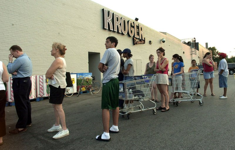 Customers wait in line to buy essential items at a grocery store in Grosse Pointe, Mich., after the blackout of August 2003.