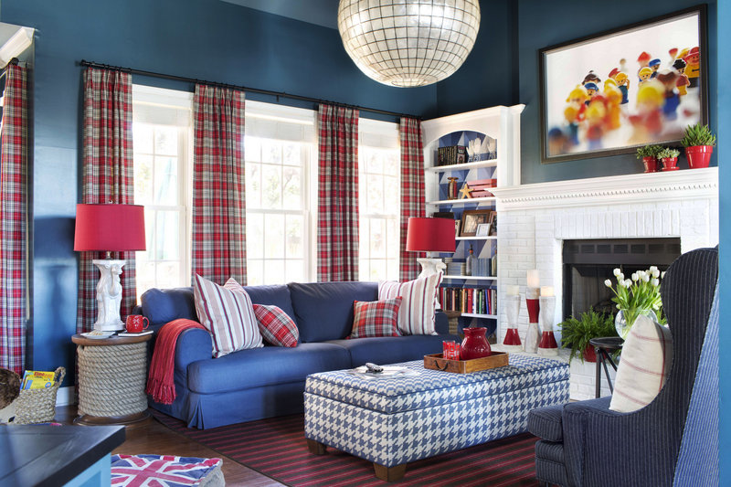 This playful family room uses youth in the decor, with original framed photography of 1980s Duplo figures and a vibrant palette of navy blue and fire engine red.