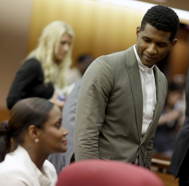 Usher greets ex-wife Tameka Foster Raymond after a hearing Friday in Atlanta. Their son, 5, had been stuck in a pool drain.
