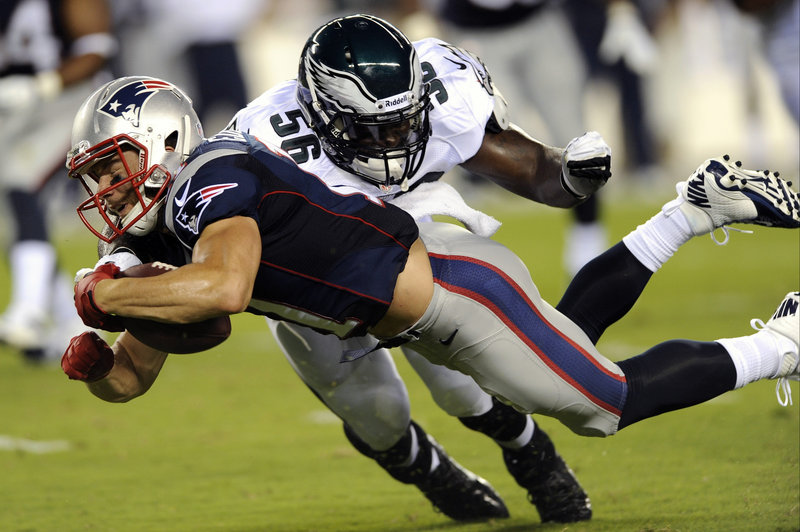 Julian Edelman of the Patriots dives for extra yardage after making a catch as Phillip Hunt of the Eagles brings him down. The Patriots won the opening exhibition game, 31-22.