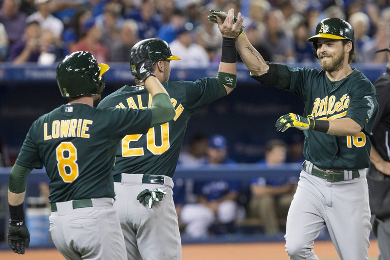 Josh Reddick of the A's is greeted by Josh Donaldson and Jed Lowrie after hitting his third home run of the game Friday in a 14-6 win over the Blue Jays at Toronto.