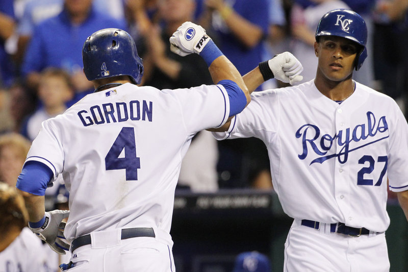 Alex Gordon of the Kansas City Royals is welcomed by Justin Maxwell after hitting a home run in the third inning Friday night of a 9-6 victory against the Boston Red Sox.