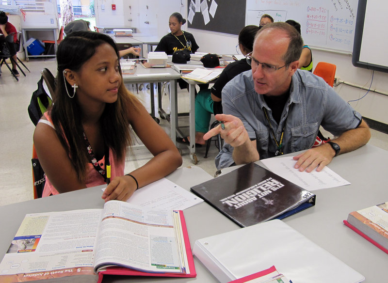 Teacher Dennis Tynan, right, talks to student Chyda Iokua at Nakakuli High and Intermediate School in Waianae, Hawaii, Aug. 9. Hawaii is finding it difficult to staff schools.