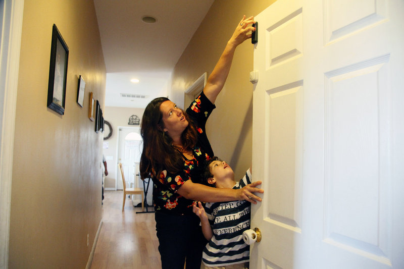 Jo Ashline sets a door lock, accompanied by her son, Andrew, 11, who has autism, at their home in Orange, Calif.