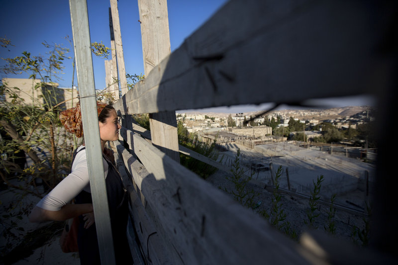 An Israeli woman looks at a construction site during a ceremony Sunday to mark the resumption of building new housing units in an east Jerusalem neighborhood.