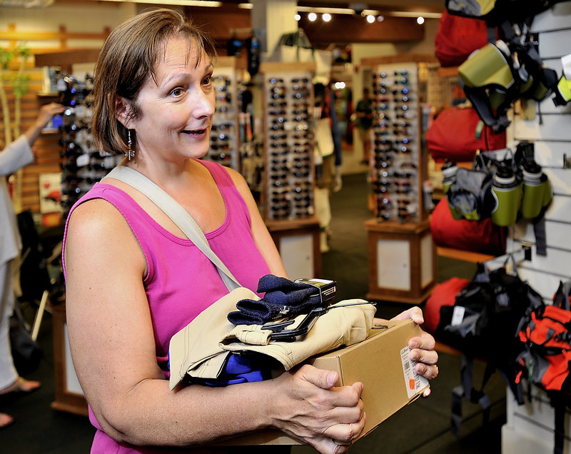 Martha Dean of Warwich, R.I., carries an armful of back-to-school items for her son, Josh, 7, at L.L. Bean in Freeport. Dean, who is vacationing in Maine, took advantage of her time here to visit Freeport's downtown retail center.