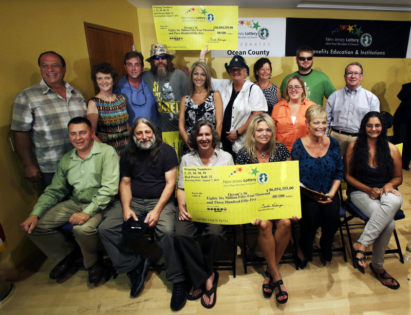 Lottery winners pose Tuesday in Toms River, N.J. The Ocean's 16, as the group of Ocean County public workers calls itself, won a third of the $448 million Powerball jackpot.