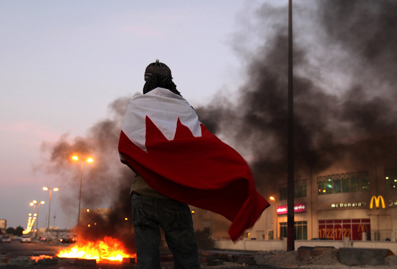 A Bahraini anti-government protester wrapped in a national flag watches tires burn Tuesday in Malkiya, Bahrain. Activists are calling for protesters to flood the streets Wednesday.