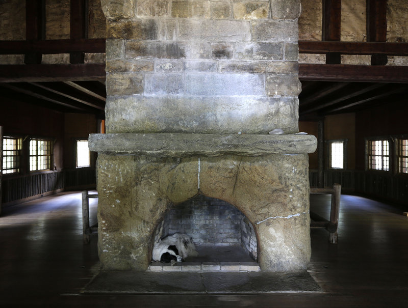 Swix, a dog owned by master carpenter Michael Frenette, naps in a fireplace in the main hall.