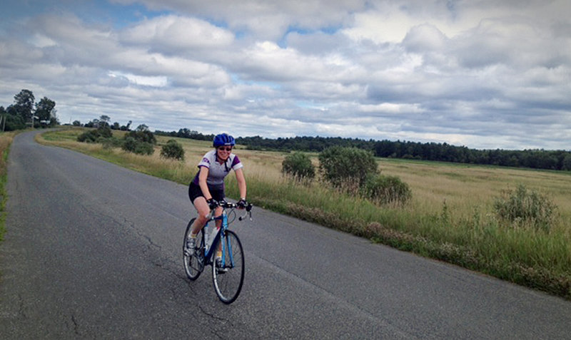 Kim True, director of BikeMaine's first 400-mile bicycle tour next month, rides along a stretch of farming country just outside Dover-Foxcroft, where some 250 bicyclists from more than 35 states will soon follow in her path.