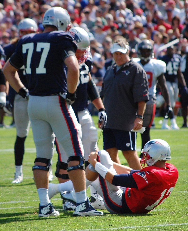 Tom Brady grabs his left knee after being knocked down during a joint workout with the Tampa Bay Buccaneers on Wednesday in Foxborough, Mass. It's the same knee Brady hurt in the 2008 opener.