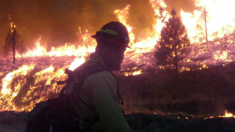 In a photo released Wednesday, a firefighter stands watch Monday near the edge of the Elk Complex fire outside Pine, Idaho. The lightning-caused fire has burned about 175 square miles.
