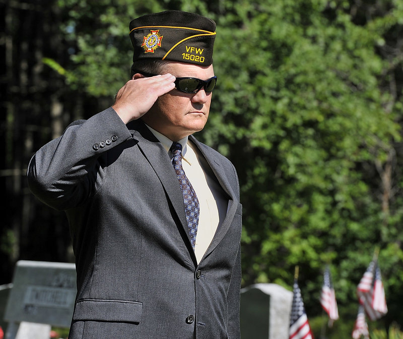 Francis Lyons, Jr. salutes during the playing of Taps for his four relatives, who were killed in past wars.