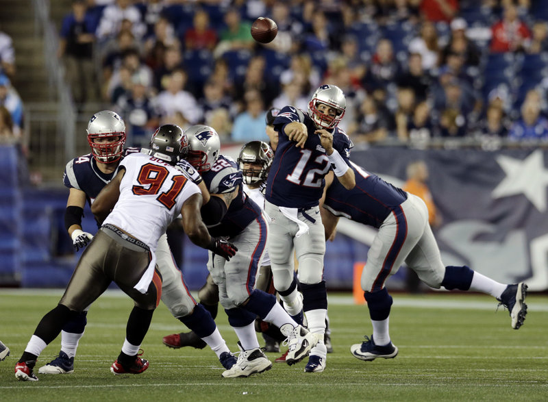 New England's Tom Brady, showing no ill effects of a sore knee, throws a touchdown pass over Tampa Bay defensive end Da'Quan Bowers to new receiver Danny Amendola during a 25-21 preseason win on Friday.
