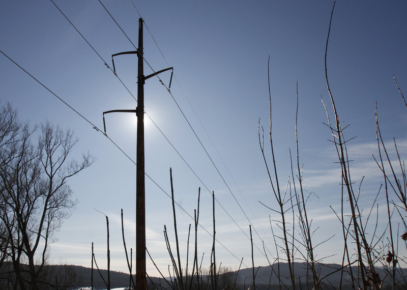 "Power lines run through Duxbury, Vt. Vermont's largest utility has been cheering the arrival of solar energy and ""net metering,"" while smaller utilities have been pushing back."