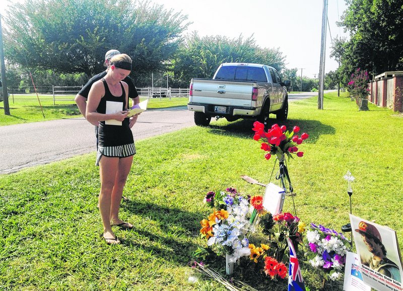 Sarah Harper, Christopher Lane's girlfriend, stands beside a memorial along the road where Lane, and Australian baseball player, was shot to death Friday in Duncan, Okla.