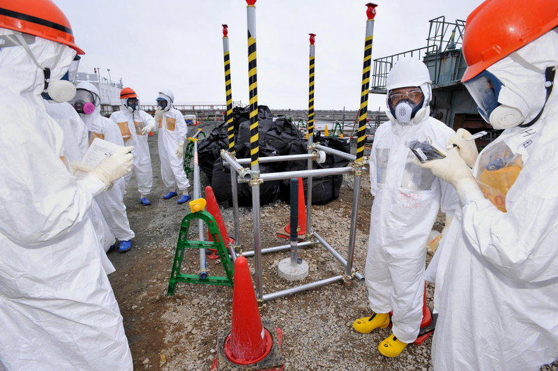 Reporters inspect an observation well, which was dug to take underground water samples near the Fukushima Dai-ichi nuclear plant in Okuma, northeastern Japan.