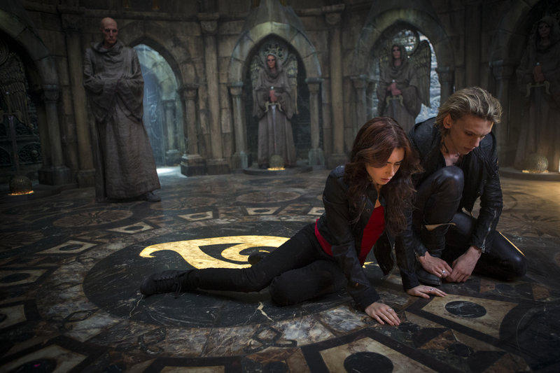 "Lily Collins and Jamie Campbell Bower in the new action-adventure film ""The Mortal Instruments: City of Bones."""