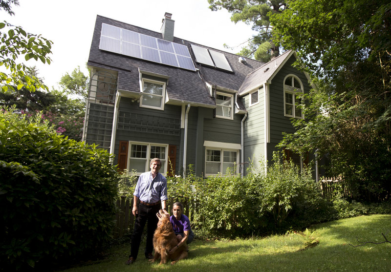 Ketch Ryan, right, and her neighbor Kirk Renaud pose next her solar-paneled house in Chevy Chase, Md.