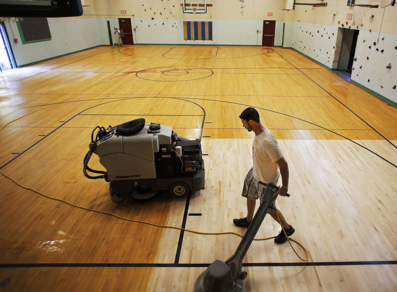 Paul Keef, foreground, and Jason Rousseau, background, of Clean-O-Rama, buff the gymnasium floor at King Middle School Wednesday, August 21, 2013, in preparation for the start of the upcoming school year.