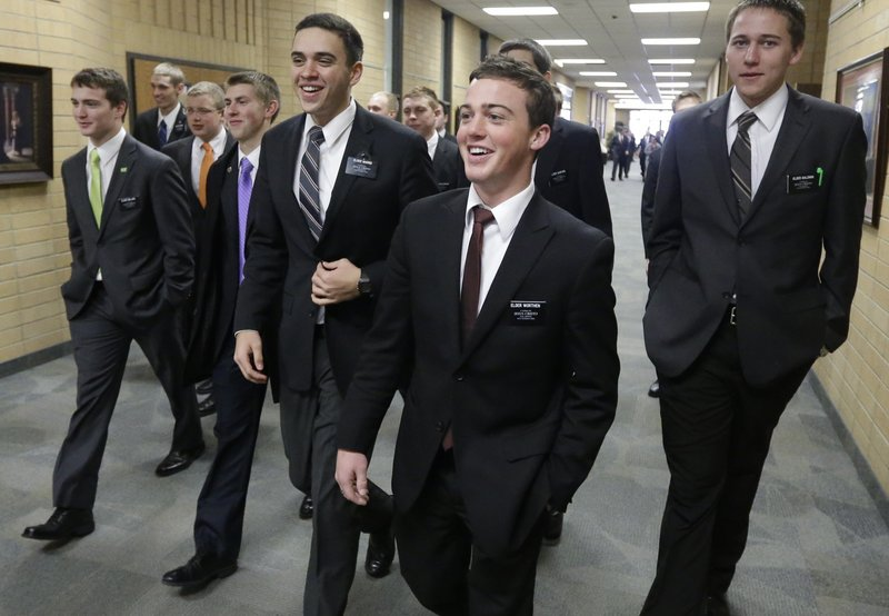 Mormon missionaries walk through the halls at the Missionary Training Center in Provo, Utah, in January. The church has lowered the minimum age for missionaries.