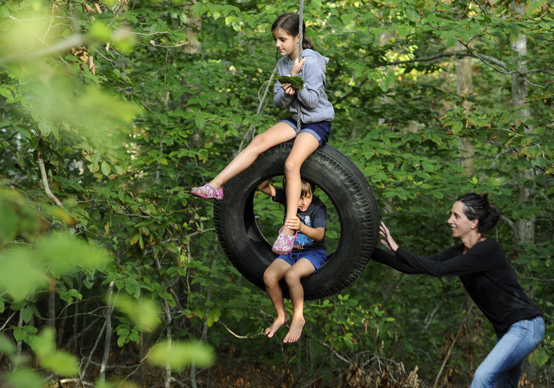 "Scientist Natalie Boelman pushes her children, Aline Waldhauser, 6, and Nico Waldhauser, 4, on a tire swing behind their cottage at Woods Hole in Falmouth, Mass., on Aug. 15. ""It's like summer camp for all of us,"" she said."