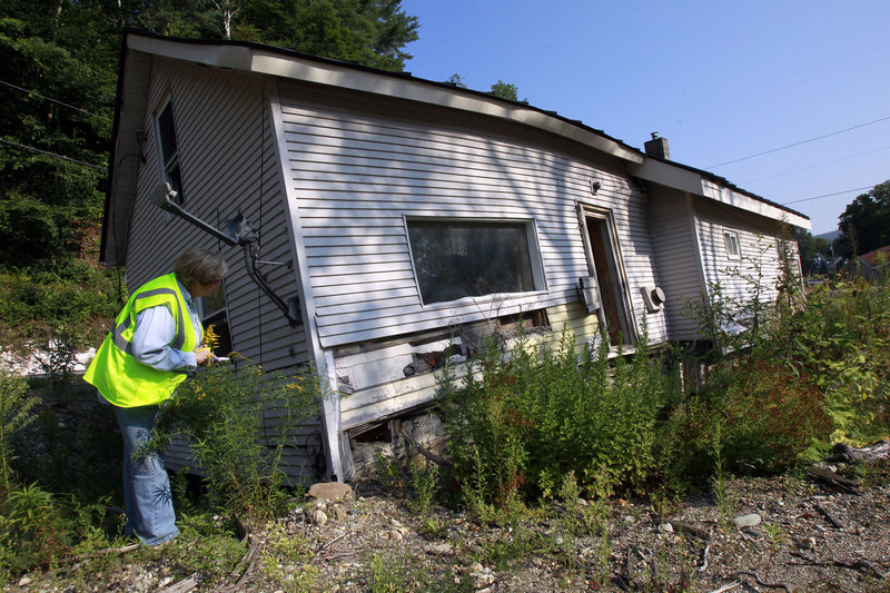 Cheryl Harvey of Harvey's Plumbing and Excavating takes notes on a house to be demolished in Pittsfield, Vt.