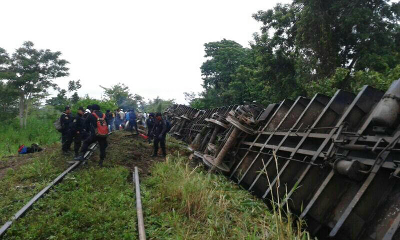 In this photo released by the Civil Protection agency in the State of Tabasco, police agents work at the site where eight of a freight train's 12 cars derailed Sunday in Mexico.