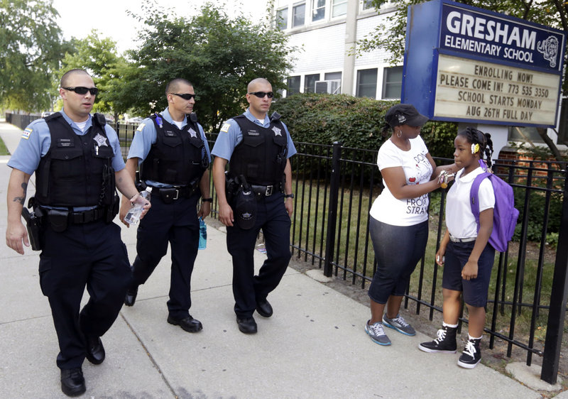 Chicago police patrol as Crystal Stovall delivers her niece Kayla Porter from their south side home to Gresham Elementary School on the first day of classes Monday.