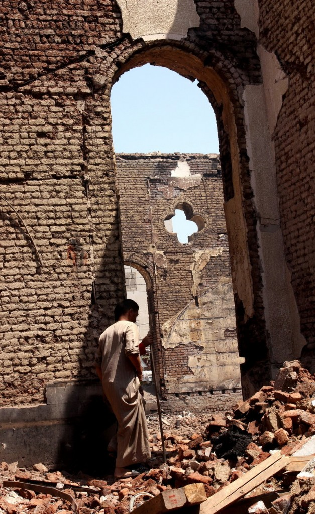 A man walks in the ruins of the Evangelical Church of Malawi, in Malawi, Egypt, on Aug. 17 after it was looted and burned by a mob.