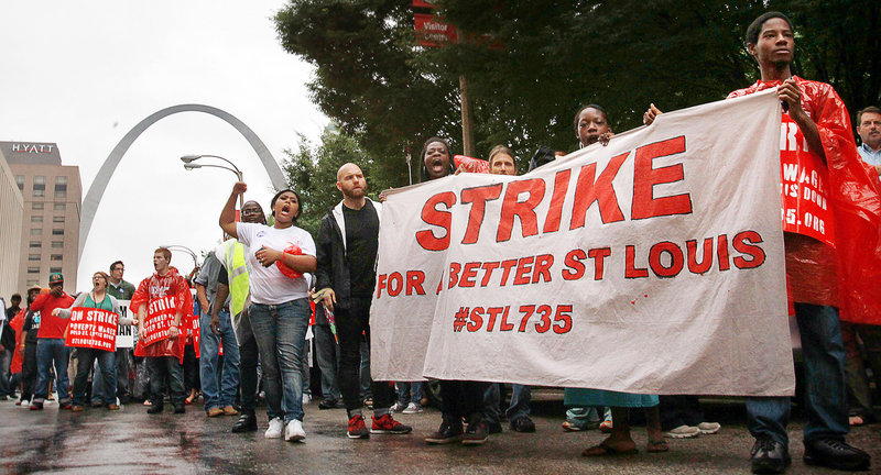 "Protesters march through downtown St. Louis to demand a higher minimum wage last month. The push to increase the minimum wage has brought attention to ""McJobs,"" which are known for their low pay and limited prospects."
