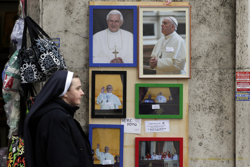 A nun walks past pictures of newly elected Pope Francis and one of Pope Emeritus Benedict XVI, top left, near the Vatican on March 15. Francis says he wants to shed the image of the Catholic Church as chauvinistic.