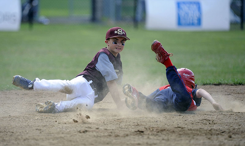 Blaze Zaniol, right, of Lincoln, R.I., dives into second base ahead of the tag by Saco's Luke Chessie during Friday's opening game at the Little League New England Regional in Bristol, Conn. Lincoln won, 11-2.