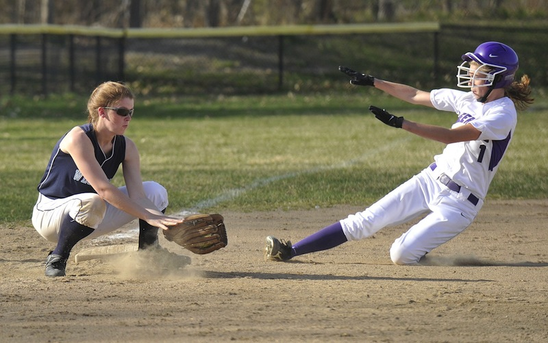 In this April 2012 file photo, Deering High's Nicole Mason slides safely into third base as Westbrook third baseman Mikaela Carey takes the throw. The U.S. Department of Education said Thursday, Sept. 27, 2013 it has reached an agreement with Portland's public schools to ensure that female students in the district will have athletic opportunities that are equal to those of boys.