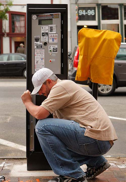 Dan Culliton installs a solar powered parking station on Commercial Street in Portland in this May 14, 2012, photo.