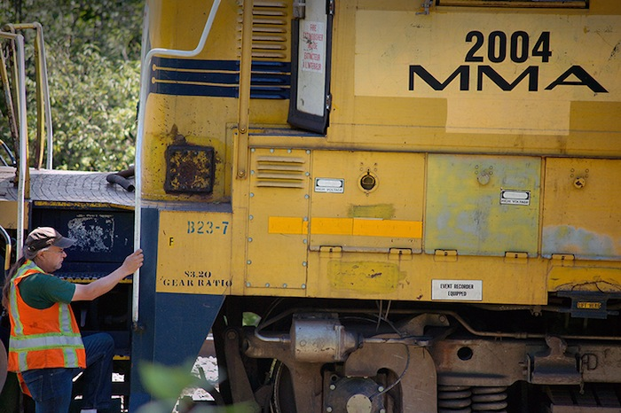 In this July 2013 file photo, a crew from Montreal, Maine & Atlantic Railway works to put a derailed locomotive back on the tracks in Brownville. The Maine railway is seeking a loan that would allow it to operate through bankruptcy.