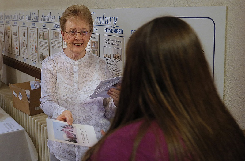 Barbara Nee, 80, who has been a lifelong parishoner at St. John the Evangelist Catholic Church in South Portland, hands out programs at the church's final Mass Wednesday night.