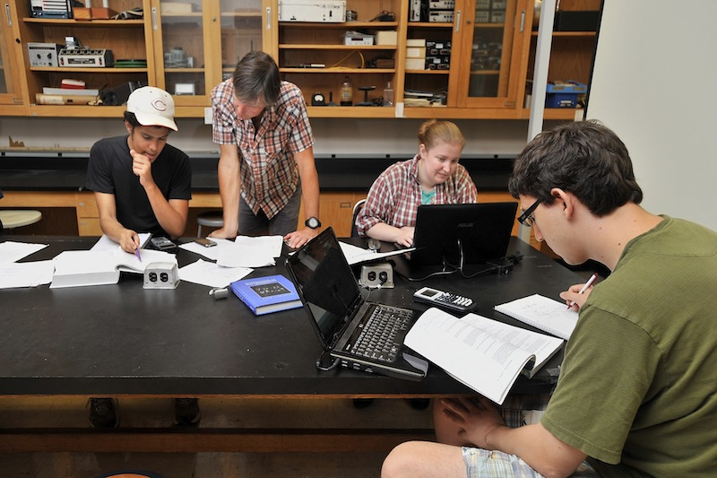 University of Southern Maine physics students work on physics problems Thursday, Sept. 13, 2013 as physics professor Paul Nakroshis, second from left, helps Ramses Damayo, left, a junior at USM. The university is eliminating the physics major because of under-utilization. Other physics majors are junior Deb Hilton, second from right, and senior Trevor Hamer, right.