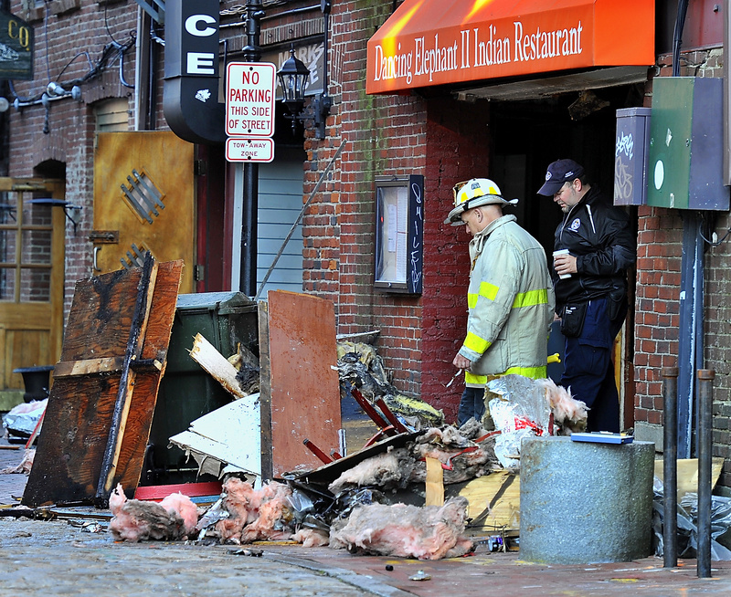 Portland Deputy Fire Chief David Jackson and a Portland health inspector survey damage from an early-morning fire Thursday in a Wharf Street building that damaged five businesses, including the Dancing Elephant II Indian restaurant.